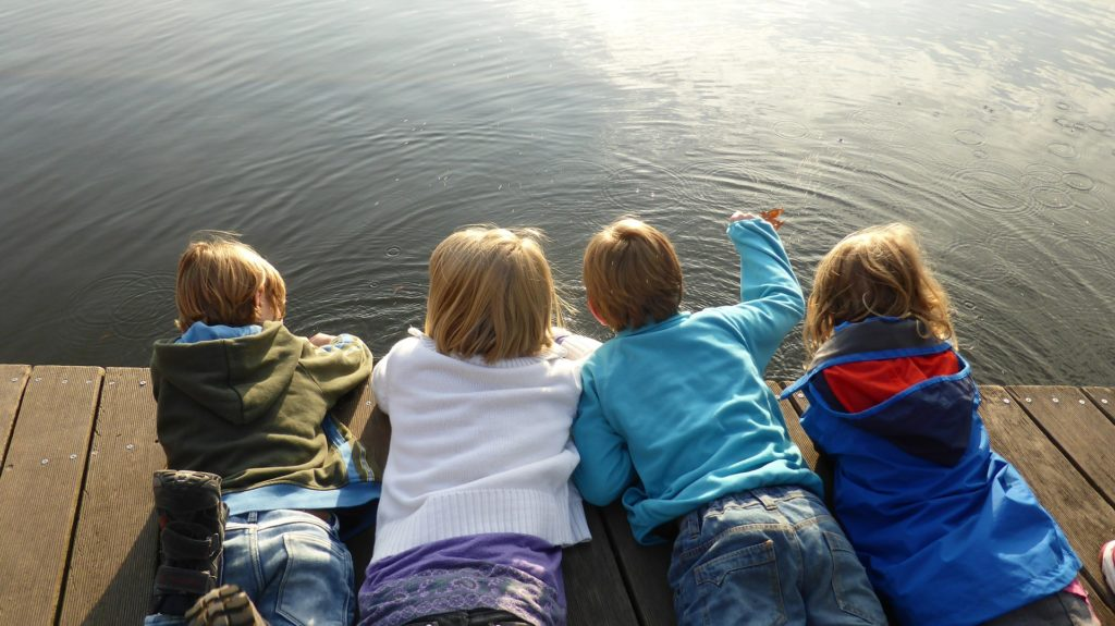Children on a dock at lake. Playtime therapy is a form of children's counseling.