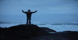 man rock staring sea