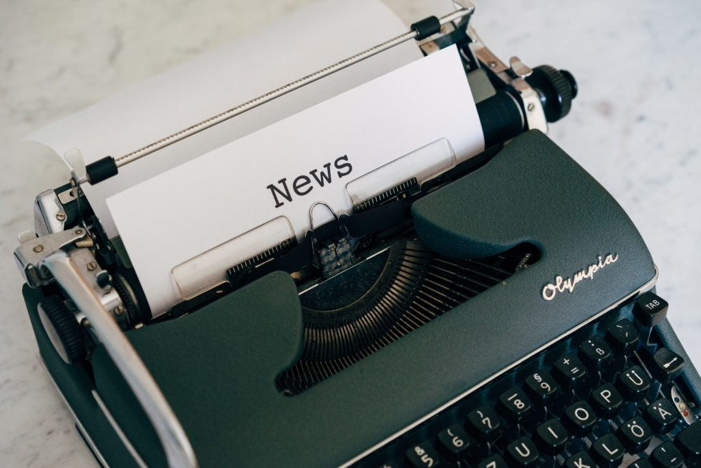 An antique typewriter taps out news for a newsletter.